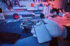 Ο ηλεκτρονικός τεχνικός κρατά ένα σύγχρονο smartphone με ένα σπασμένο σώμα, εξετάζει προσεκτικά τη ζημία χρησιμοποιώντας μια ενίσ στοκ εικόνες