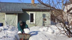 Ο ηληκιωμένος καθαρίζει το χιόνι από το σπίτι και παίρνει έξω στον κήπο απόθεμα βίντεο