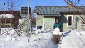 Ο ηληκιωμένος καθαρίζει το χιόνι από το σπίτι στο τέλος ενός χιονώδους χειμώνα απόθεμα βίντεο