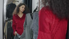 Ο θηλυκός αγοραστής συγκρίνει δύο διαφορετικά χρώματα φορεμάτων στο μεταβαλλόμενο δωμάτιο απόθεμα βίντεο