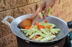 Ο θηλυκός αρχιμάγειρας βάζει τα αγγούρια και τα καρότα στο καυτό τηγάνι για το γλυκόπικρο ανακατώνω-τηγανισμένο χοιρινό κρέας ή P στοκ φωτογραφία