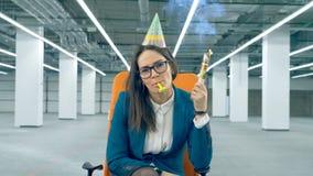 Ο θηλυκός υπάλληλος εκρήγνυται μια κροτίδα κομμάτων, που φορά έναν εορτασμό ΚΑΠ Θαμπή έννοια γενεθλίων φιλμ μικρού μήκους