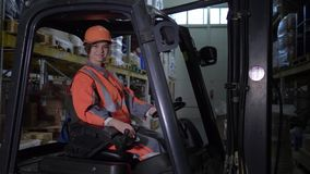 Ο θηλυκός forklift οδηγός φορτηγού στο σκληρό κράνος και ομοιόμορφος εξετάζει τη κάμερα και χαμογελά στην αποθήκη εμπορευμάτων φιλμ μικρού μήκους