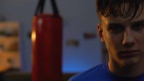 Ο ιδρωμένος έφηβος κοιτάζει σοβαρά μετά από τον εντατικό εγκιβωτισμό workout, αντιμετωπίζοντας την πρόκληση απόθεμα βίντεο