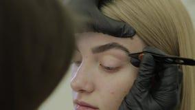 Ο καλλιτέχνης Makeup μαδά τα φρύδια ενός νέου κοριτσιού σε ένα σαλόνι ομορφιάς απόθεμα βίντεο