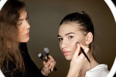 Ο καλλιτέχνης Makeup το γοητευτικό κορίτσι κάνει makeup σε ένα όμορφο νέο κορίτσι στοκ εικόνες