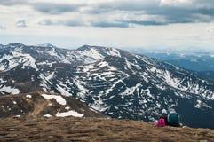 Ο καλύτερος φίλος δύο κάθεται στη χλόη στη λίμνη και το βουνό στοκ εικόνες