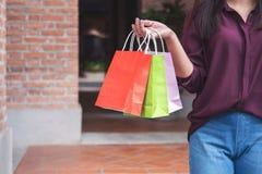 Ο καταναλωτής και η έννοια τρόπου ζωής αγορών, ευτυχής νέα γυναίκα που στέκεται και που κρατά τις ζωηρόχρωμες αγορές τοποθετούν ν στοκ φωτογραφία με δικαίωμα ελεύθερης χρήσης