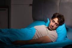 Ο κουρασμένος εξαντλημένος ύπνος ατόμων στο κρεβάτι του στοκ εικόνα με δικαίωμα ελεύθερης χρήσης