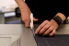 ο κύριος κόβει το ύφασμα nesting Ταιριάζοντας το ύφασμα που μαρκάρεται με την άσπρη κιμωλία κοπή και ράψιμο στοκ εικόνα