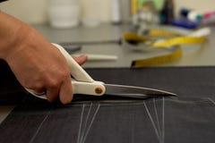 ο κύριος κόβει το ύφασμα nesting Ταιριάζοντας το ύφασμα που μαρκάρεται με την άσπρη κιμωλία κοπή και ράψιμο στοκ εικόνες