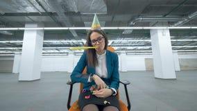 Ο λυπημένος θηλυκός διευθυντής κάθεται σε ένα καπέλο γενεθλίων και ρίχνει το κομφετί απόθεμα βίντεο