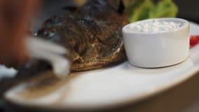 Ο μάγειρας βάζει τα μαγειρευμένα ψάρια σκουμπριών στο μεγάλο πιάτο με την άσπρα σάλτσα, το λεμόνι, το πιπέρι και το μαρούλι σε το απόθεμα βίντεο