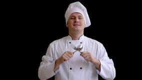 Ο μάγειρας κρατά τα χέρια του με ένα κουτάλι και ένα δίκρανο θωρακικό σε επίπεδο και αρχίζει να χτυπά και να κινείται απόθεμα βίντεο