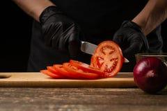 Ο μάγειρας κόβει τη φρέσκια ντομάτα στην κινηματογράφηση σε πρώτο πλάνο για να δημιουργήσει burger, ένα χάμπουργκερ Στο κλίμα με  στοκ φωτογραφία