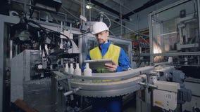 Ο μηχανικός ελέγχει τα μπουκάλια που κινούνται σε μια γραμμή εγκαταστάσεων, αυτοματοποιημένος εξοπλισμός απόθεμα βίντεο