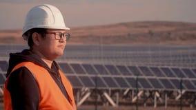 Ο μηχανικός της ασιατικής εμφάνισης σε μια πορτοκαλιά φανέλλα και ένα σκληρό καπέλο επιθεωρεί την περιοχή αφότου κάνει τις σημαντ απόθεμα βίντεο