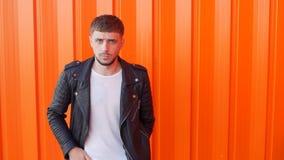 Ο μοντέρνος τύπος με μια γενειάδα στέκεται σε ένα πορτοκαλί υπόβαθρο και κυματίζει επικεφαλής όχι του, σε αργή κίνηση, διάστημα α απόθεμα βίντεο