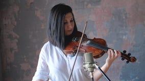 Ο μουσικός γυναικών στο άσπρο πουκάμισο αποδίδει με ένα βιολί απόθεμα βίντεο