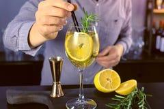 Ο μπάρμαν βάζει τα άχυρα στο κοκτέιλ οινοπνεύματος με το λαμπιρίζοντας κρασί, τον πάγο και το ποτό wineglass, άποψη κινηματογραφή στοκ εικόνα