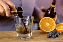 Ο μπάρμαν χύνει το kahlua από το ποτηράκι στο γυαλί βράχων με το tequila προετοιμάζοντας το κοκτέιλ οινοπνεύματος Κινηματογράφηση στοκ εικόνες