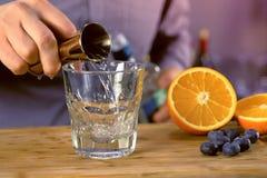 Ο μπάρμαν χύνει το tequila από το ποτηράκι στο γυαλί βράχων προετοιμάζοντας το κοκτέιλ οινοπνεύματος Κινηματογράφηση σε πρώτο πλά στοκ εικόνα με δικαίωμα ελεύθερης χρήσης