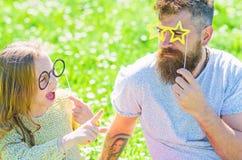 Ο μπαμπάς και η κόρη κάθονται στη χλόη στο grassplot, πράσινο υπόβαθρο Η οικογένεια ξοδεύει τον ελεύθερο χρόνο υπαίθρια Τοποθέτησ στοκ φωτογραφία με δικαίωμα ελεύθερης χρήσης