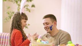 Ο μπαμπάς και η κόρη λεκιάζουν ο ένας τον άλλον με το χρώμα, διακοσμώντας τα αυγά Πάσχας απόθεμα βίντεο