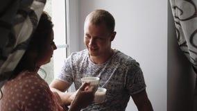 Ο νέοι ερωτευμένοι άνδρας και η γυναίκα ζευγών πίνουν τον καφέ κοντά στο παράθυρο 1 απόθεμα βίντεο