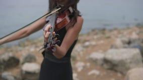 Ο νέος βιολιστής στο μαύρο φόρεμα παίζει κοντά στη θάλασσα όμορφο βιολί κοριτσιών φιλμ μικρού μήκους