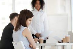 Ο νέος εργαζόμενος αισθάνεται ματαιωμένος κατά τη διάρκεια της συνεδρίασης στην εργασία στοκ εικόνα με δικαίωμα ελεύθερης χρήσης