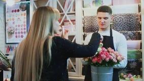 Ο νέος εύθυμος άνδρας και οι όμορφοι ανθοκόμοι γυναικών μιλούν στον πελάτη και δίνουν τις συμβουλές φιλμ μικρού μήκους