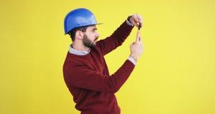 Ο νέος μηχανικός με ένα μπλε κράνος στο στούντιο με έναν κίτρινο τοίχο υποβάθρου παίρνει τις εικόνες κάτι χρησιμοποίηση φιλμ μικρού μήκους
