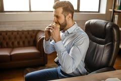 Ο νέος όμορφος επιχειρηματίας τρώει burger στο γραφείο του Κάθεται στο γεύμα πινάκων και δαγκωμάτων Ανθυγειινός εύγευστος πασπαλί στοκ φωτογραφίες με δικαίωμα ελεύθερης χρήσης