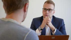 Ο νέος υπάλληλος διευθυντών με τον πελάτη κάθεται στον πίνακα γραφείων Συνομιλία δύο νέων λαών Ο επιχειρηματίας κάνει τη διαπραγμ φιλμ μικρού μήκους