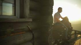 Ο νεαρός άνδρας κάθεται κοντά στο παλαιό ξύλινο σπίτι Ακτίνες ήλιων κίνηση αργή απόθεμα βίντεο
