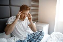 Ο νεαρός άνδρας κάθεται στο κρεβάτι το πρωί Έχει τον πονοκέφαλο Χέρια λαβής τύπων στο κεφάλι Ζαλισμένος και επίπονος στοκ φωτογραφίες με δικαίωμα ελεύθερης χρήσης