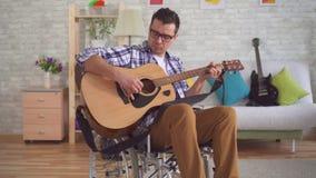 Ο νεαρός άνδρας καθιστούσε ανίκανος το μουσικό σε μια κιθάρα παιχνιδιού αναπηρικών καρεκλών απόθεμα βίντεο