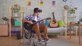 Ο νεαρός άνδρας καθιστούσε ανίκανος το μουσικό στα γυαλιά αναπηρικών καρεκλών και εικονικής πραγματικότητας που παίζει την κιθάρα απόθεμα βίντεο