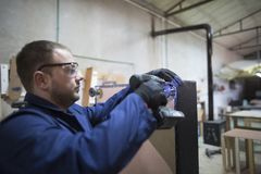 Ο νεαρός άνδρας σε ένα εργοστάσιο επίπλων συνδέει το πόδι καναπέδων στοκ εικόνα με δικαίωμα ελεύθερης χρήσης