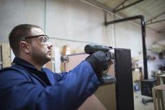 Ο νεαρός άνδρας σε ένα εργοστάσιο επίπλων συνδέει το πόδι καναπέδων στοκ φωτογραφία με δικαίωμα ελεύθερης χρήσης