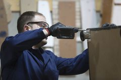 Ο νεαρός άνδρας σε ένα εργοστάσιο επίπλων συνδέει το πόδι καναπέδων στοκ εικόνες