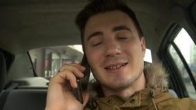 Ο νεαρός άνδρας στο αυτοκίνητο μιλά στο τηλέφωνο απόθεμα βίντεο