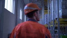 Ο νεαρός άνδρας στο πορτοκαλί κράνος και τα ομοιόμορφα περάσματα μέσω της μεγάλης αποθήκης εμπορευμάτων και επιθεωρεί τα ράφια με απόθεμα βίντεο