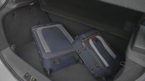 Ο νεαρός άνδρας που πιέζει χρονικά φορτώνοντας τον κορμό αυτοκινήτων του σε μια βιασύνη με τις τσάντες ταξιδιού ανησύχησε για την φιλμ μικρού μήκους