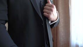 Ο νεόνυμφος κρατά τα χρυσά γαμήλια δαχτυλίδια στο χέρι του και τα βάζει στην τσέπη σακακιών του Κινηματογράφηση σε πρώτο πλάνο Έν απόθεμα βίντεο