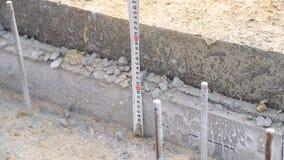 Ο οικοδόμος μετρά το ύψος του σκυροδέματος στο εργοτάξιο οικοδομής απόθεμα βίντεο
