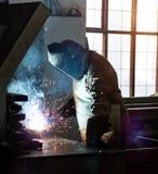 Ο οξυγονοκολλητής στο εργοστάσιο σε μια μάσκα συγκόλλησης ενώνει στενά τα μέρη μετάλλων, συγκόλληση και σπινθήρες, βιομηχανικοί στοκ εικόνα