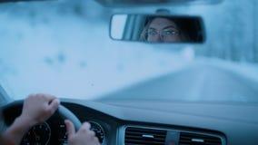 Ο οδηγός γυναικών ρυθμίζει τον οπισθοσκόπο καθρέφτη την κρύα ημέρα απόθεμα βίντεο