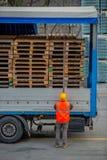 Ο οδηγός φορτηγού εξασφαλίζει τη φόρτωση των μπουκαλιών του μεταλλικού νερού με τη δέσμευση της με τα σχοινιά πρίν αρχίζει τη μετ στοκ εικόνες